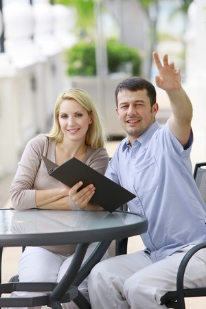 Man with menu raising his hand, woman smiling beside him photo