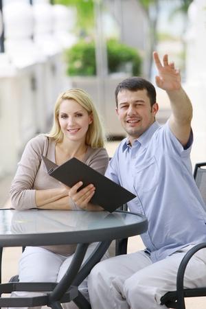 Man with menu raising his hand, woman smiling beside him photo