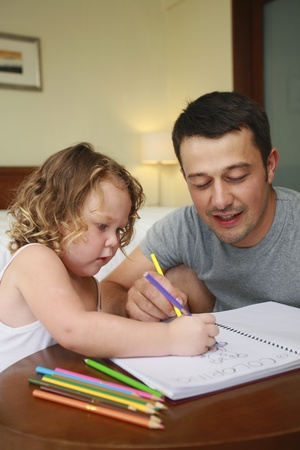 Man helping his daughter to colour photo