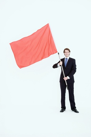 Businessman standing with red flag in his hands photo
