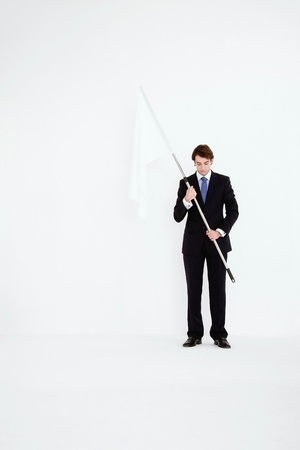Businessman holding a while flag Stock Photo - 9043161