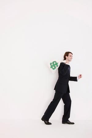 Businessman carrying a money bag over his shoulder photo