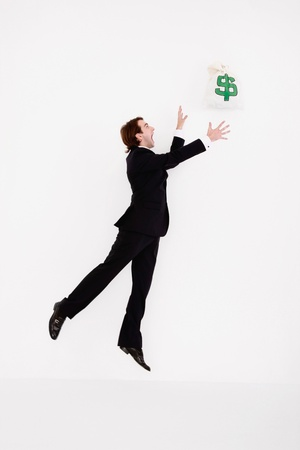 Businessman jumping up to catch a money bag photo