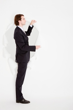 Businessman coming out through a hole torn in paper Stock Photo - 9041487