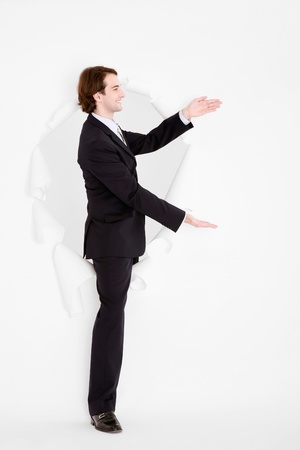 Businessman coming out through a hole torn in paper making hand gestures Stock Photo - 9042677