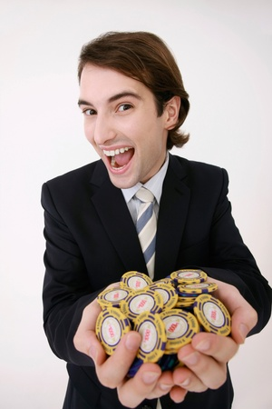 Businessman holding a handful of gambling chips photo