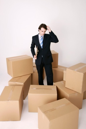 Businessman standing among cardboard boxes scratching his head Stock Photo - 9041576