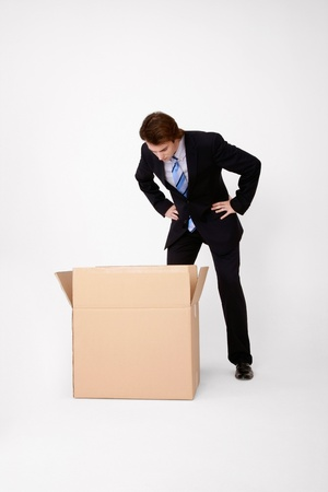 Businessman looking into opened cardboard box photo