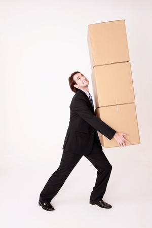 Businessman carrying a stack of cardboard boxes photo