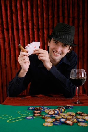 Man holding up four Aces in casino photo