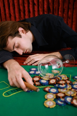 Drunk man lying on gaming table in casino photo