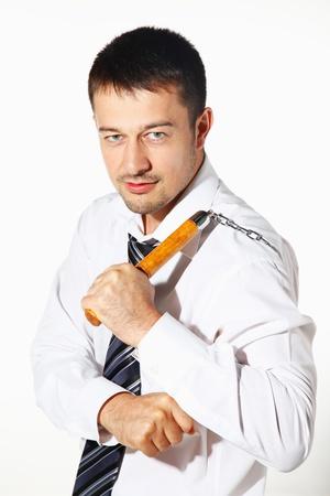 nunchaku: Businessman holding nunchaku behind back