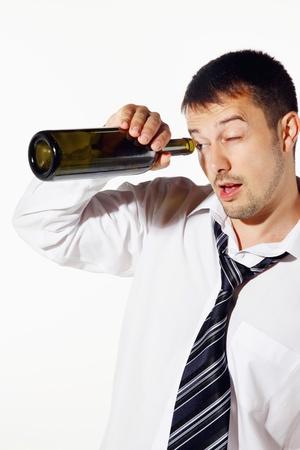 Drunk businessman peeping into a bottle