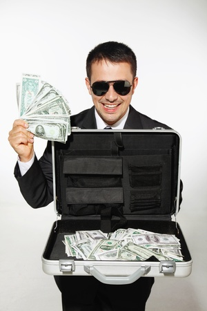 abundance money: Businessman with sunglasses showing a briefcase of money