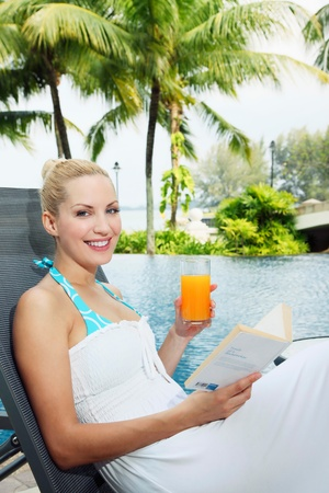 Woman sitting on lounge chair by the pool reading a book photo