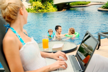 eastern european ethnicity: Woman using laptop looking at her family in the pool