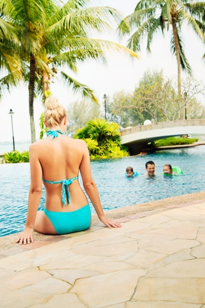 Woman in bikini sitting at the edge of pool watching her family swim photo
