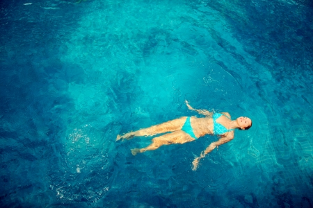 woman floating: Woman swimming in pool Stock Photo