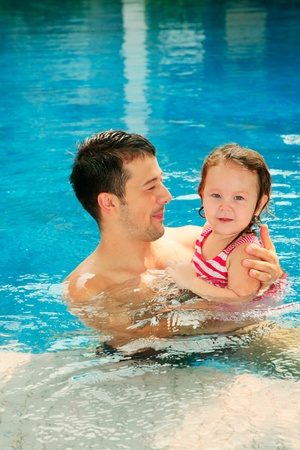 Man and daughter swimming in the pool photo