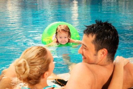 Man and woman relaxing at the edge of pool, girl watching them photo