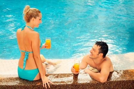 central european ethnicity: Hombre y mujer relajante en el borde de la piscina con vasos de jugo de naranja