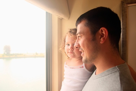 Man carrying his daughter while looking out the window photo
