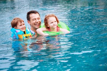 ni�os nadando: Hombre y ni�os nadando en la piscina