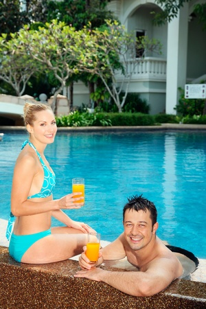 Man and woman relaxing at the edge of pool with glasses of orange juice photo
