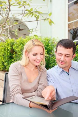 Family looking at menu at an outdoor restaurant Stock Photo