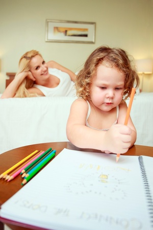 Girl drawing on coloring book, woman lying on bed in the background photo