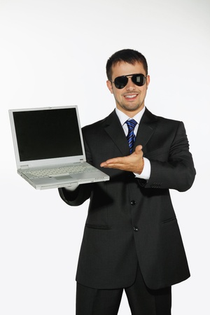 Businessman with sunglasses showing a laptop photo