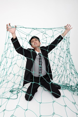Businessman trapped under a net Stock Photo - 9288099