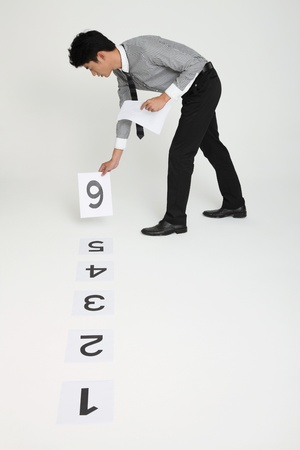 Businessman arranging numbered papers on the ground photo