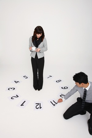 Businesswoman in circle of numbered papers while businessman pulling paper with number 11 Stock Photo - 9287916
