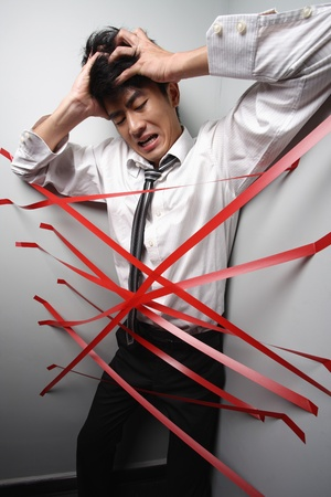 Businessman trapped at the corner of a wall by adhesive tapes Stock Photo - 9288793