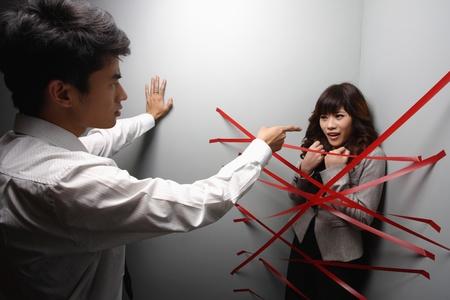 Empresario apuntando a la empresaria atrapado en la esquina de un muro por cintas adhesivas