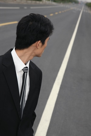 Businessman on road looking behind photo