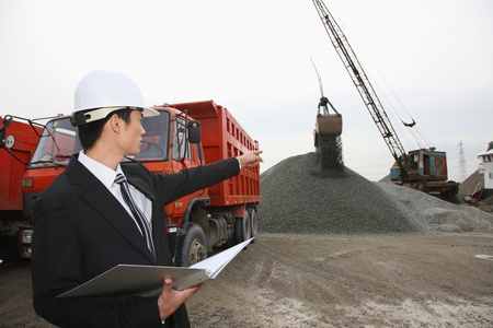 Businessman with hardhat on construction site, pointing at crane photo