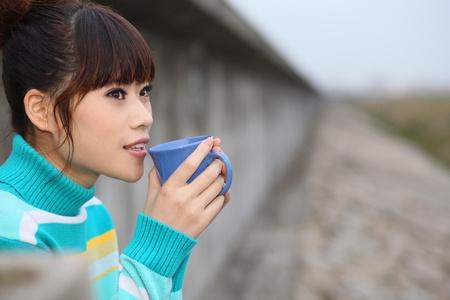Woman enjoying a cup of tea outdoors Stock Photo - 9288539