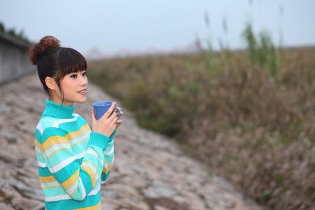 Woman enjoying a cup of tea outdoors Stock Photo - 9288537