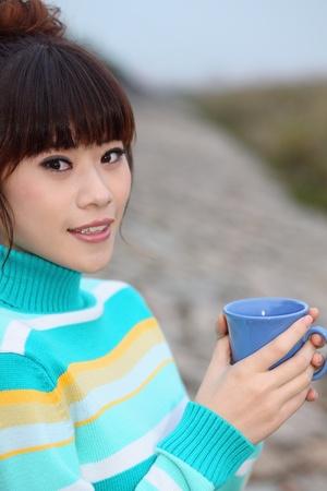 Woman enjoying a cup of tea outdoors Stock Photo - 9288535