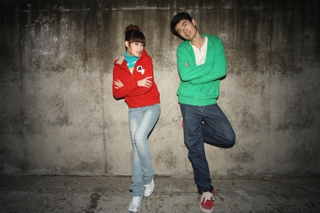 Man and woman in hooded shirts posing outdoors photo