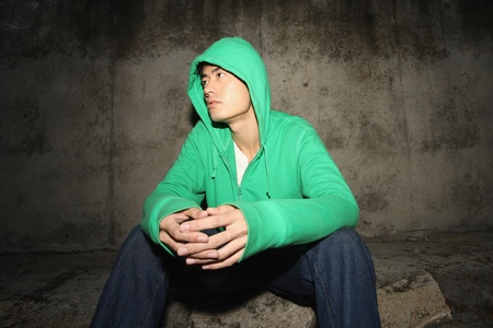 Man in hooded shirt sitting on the ground outdoors photo