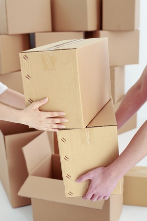 carrying girlfriend: Woman stacking cardboard boxes in mans arms Stock Photo