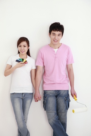 Woman holding color swatch with man holding a paint roller beside her Stock Photo - 9288072