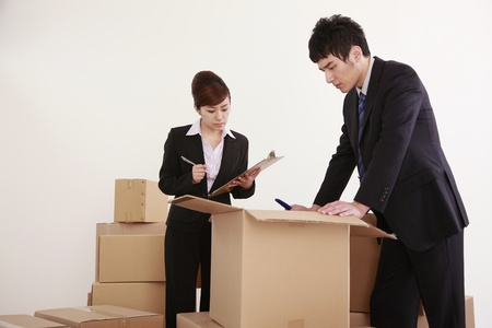 Businessman and businesswoman looking inside opened cardboard box photo