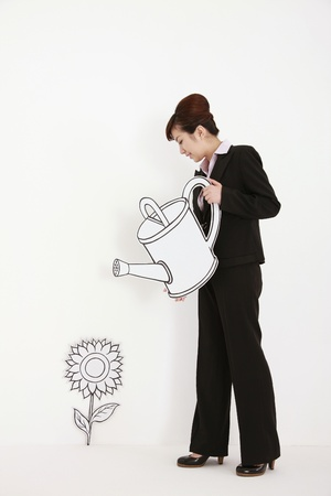 Businesswoman watering plant with watering can photo