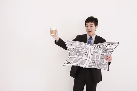 Businessman reading newspaper and holding a cup of coffee photo
