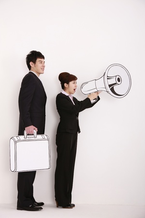 Businesswoman shouting into megaphone, businessman holding briefcase standing behind her photo