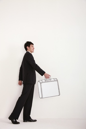 Businessman walking with briefcase in hand photo